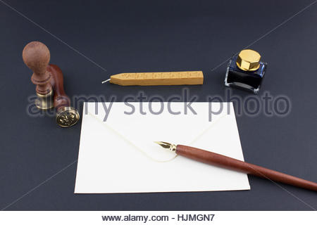 Pens, ink pot, papyrus and blotting paper on a brown table - Stock Photo