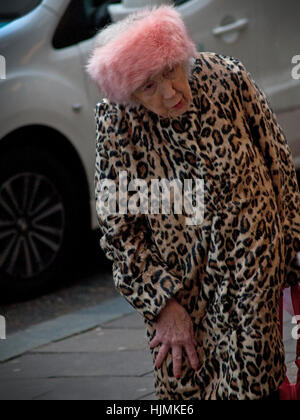 An old lady wearing a leopard skin coat on a cold street in Brighton - Stock Photo