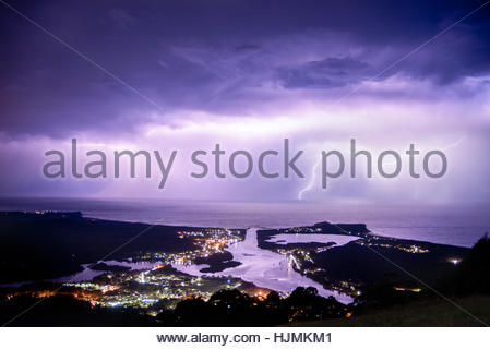 Lightning over the ocean with Laurieton in the foreground. - Stock Photo