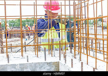 Zrenjanin, Vojvodina, Serbia - May 29, 2015: Construction worker is drilling reinforced concrete in building foundation - Stock Photo