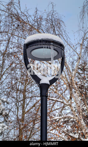 Frozen street light with icicles in cold winter day closeup - Stock Photo