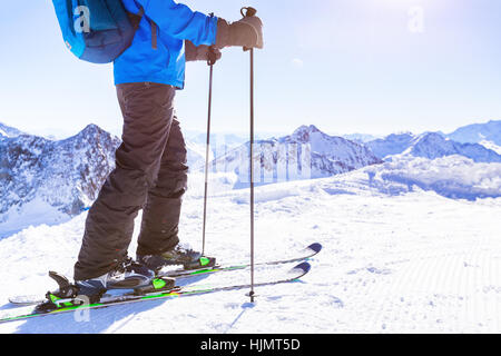 Close-up of skier boots and skis on snow trail with a beautiful white sunny winter mountain landscape in background - Stock Photo