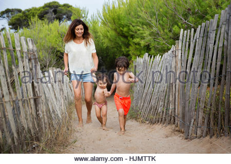 Happy mother and two children walking hand in hand on beach path - Stock Photo