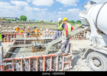Zrenjanin, Vojvodina, Serbia - May 29, 2015: Workers at building site are pouring concrete in mold from mixer truck. - Stock Photo