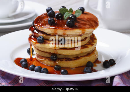 Pancake with fresh blueberries, mint and maple syrup on a white plate closeup. horizontal - Stock Photo