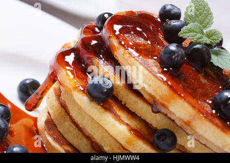 Pancake delicious with fresh blueberries, mint and maple syrup macro. horizontal - Stock Photo