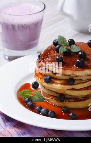Blueberry pancakes drenched with maple syrup and a cocktail close-up on the table. vertical - Stock Photo