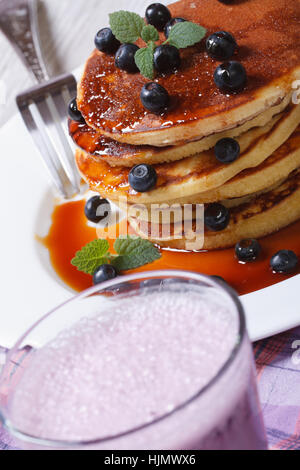 Blueberry cocktail and pancakes with berries and maple syrup on the table closeup. vertical - Stock Photo