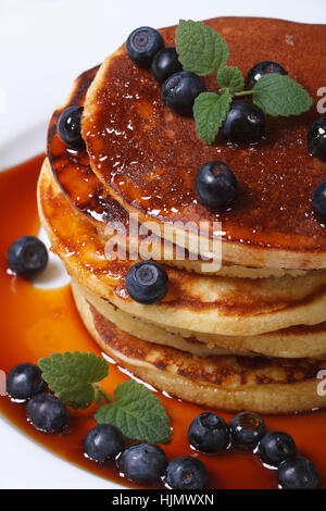 Blueberry pancakes with berries and maple syrup on the table closeup. vertical view from above - Stock Photo
