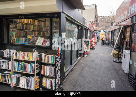 An alley converted in a shopping arcade using shipping containers, featuring a used bookstore, in the Bushwick neighborhood - Stock Photo
