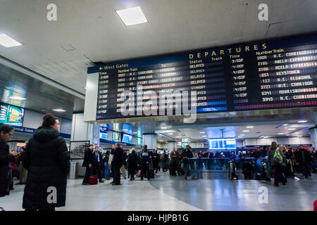 Travelers for Amtrak and NJ Transit in Penn Station in New York on Monday, January 23, 2017 wait by the departure - Stock Photo