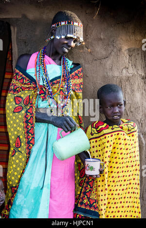 Maasai Woman pouring milk for a child, wearing traditional attire, in a village near the Masai Mara National Park, - Stock Photo