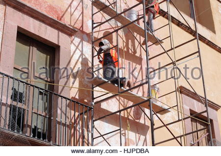 Construction workers on scaffolding in Mexico doing routine stucco cement wall restoration in bright sunlight with - Stock Photo
