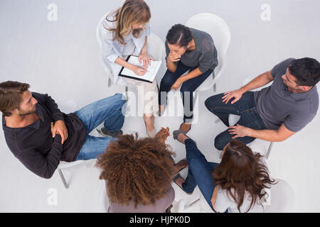 Therapist listening to patient during group therapy session - Stock Photo