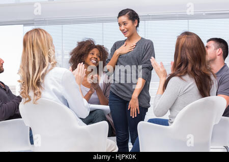 Smiling patient standing and telling her problems during therapy group session - Stock Photo