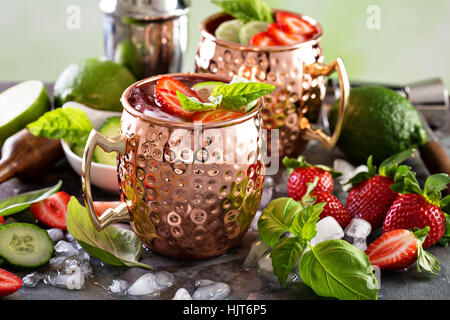 Moscow mule cocktail with lime and strawberry - Stock Photo