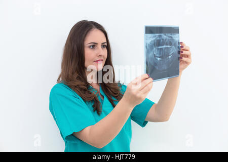 Female dentist showing her patient x-ray radiography, in the Dental Clinc - Stock Photo