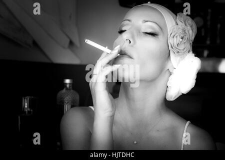 Portrait of a woman with retro hairstyle. Woman with cigarette. Fashion photo. Flowers on head. Resembling inflorescence. - Stock Photo