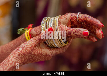 Hands of Indian bride hands painted with henna, bangles, India - Stock Photo