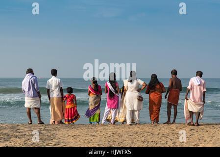 Group of Indian people in front of sea, Varkala Papanasham Beach, Kerala, India - Stock Photo