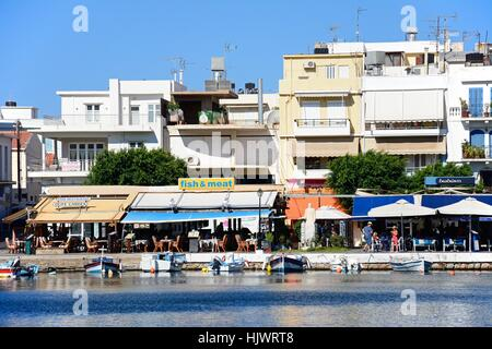 Fishing boats in the inner harbour with waterfront restaurants to the rear, Agios Nikolaos, Crete, Greece, Europe. - Stock Photo