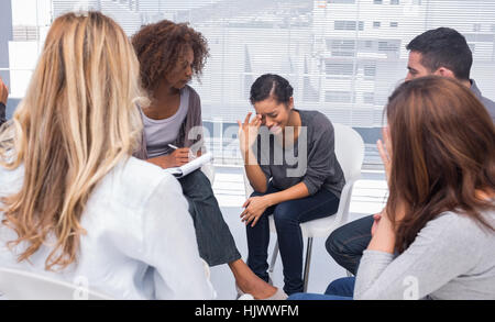 Patient crying during group therapy - Stock Photo