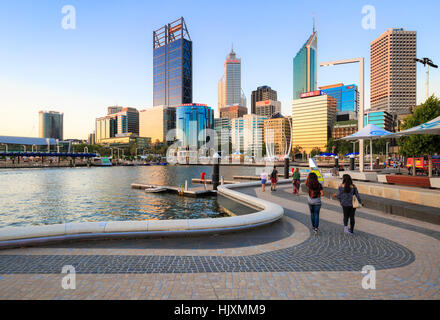 People walking along along a footpath beside the Swan River at Elizabeth Quay. - Stock Photo