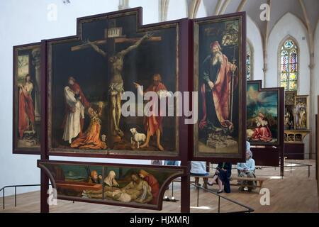 Visitors in front of the Isenheim Altarpiece (1512–1516) by German Renaissance painter Matthias Grunewald displayed - Stock Photo
