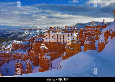 The late afternoon sun splashes across snow-covered hoodoos along the Navajo Loop Trail, Bryce Canyon National Park - Stock Photo