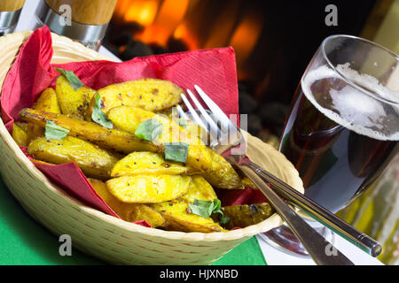 Vegan/vegetarian Bombay spiced baked potato wedges served in a basket. - Stock Photo