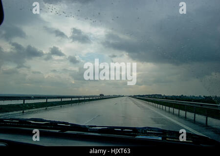 A rainy road and through the windshield - Stock Photo