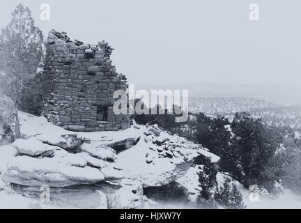 Painted Hand Tower, an Anasazi ruin, overlooking Hovenweep Canyon during a snow storm. Black and white photograph. - Stock Photo