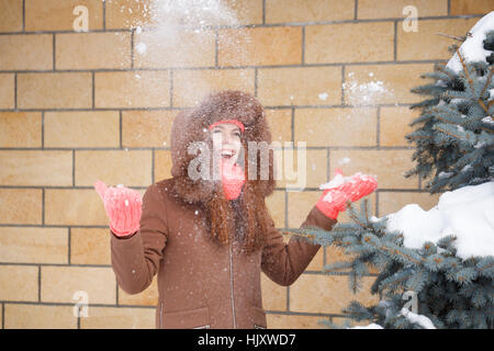 Cute teen girl in pink knitted gloves, hats and scarves, fur hooded jacket winter walks in the park. She throws - Stock Photo