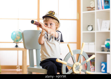 Kid boy dressed like a captain or sailor plays on chair as ship in his room. Child looks through telescope. - Stock Photo