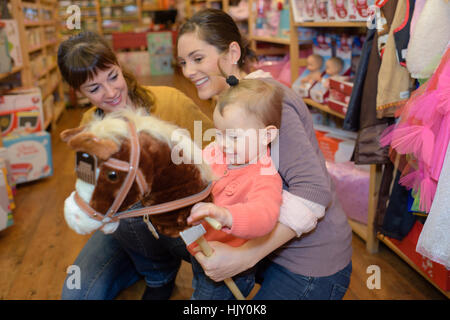 mother and daughter with attractive vendor in toy store - Stock Photo