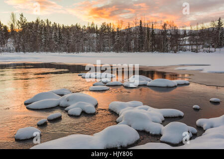 Wassara river with colorful sky reflecting in the water and rock with snow on them, Mount Dundret in background, - Stock Photo