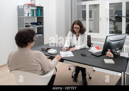 Doctor consulting senior female patient - Stock Photo
