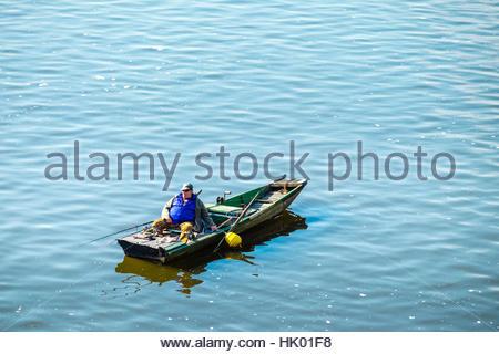 Czech Republic, Prague, Mala Strana. Man fishing on the Vltava River at sunrise. - Stock Photo