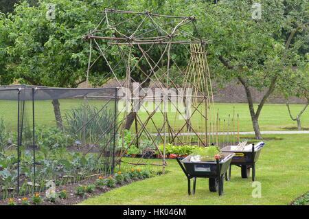 Two wheelbarrows in the garden - Stock Photo