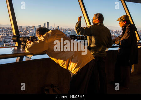 photographers on the top of a skyscraper, shooting photos of the skyline at sunset Tokyo, Japan - Stock Photo