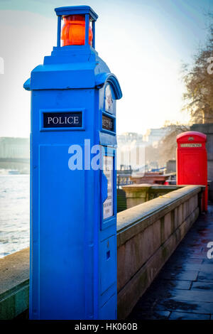 An old fashioned police box and telephone box stand along London's River Thames - Stock Photo