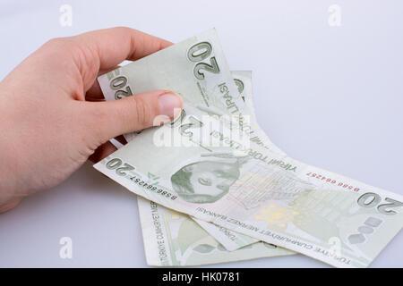 Hand holding 20 Turksh Lira banknote  on white background - Stock Photo