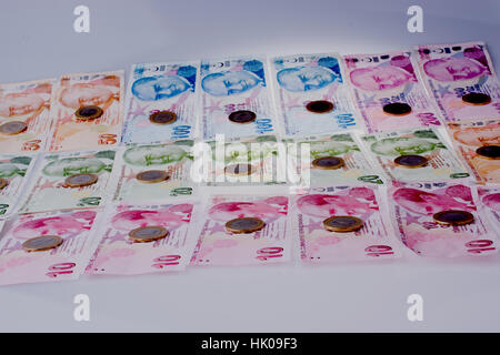 Coins on the Turksh Lira banknotes of various color, pattern and value on white background - Stock Photo