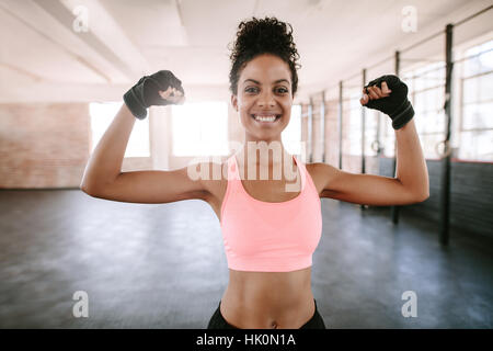 Portrait of young fitness woman flexing muscles and smiling. African female model in sportswear showing her muscles. - Stock Photo