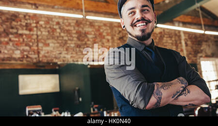 Close up of happy young male barber with cap looking away and smiling. Handsome hairdresser in salon. - Stock Photo