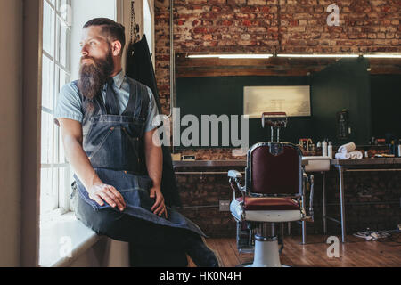 Young barber at his barbershop. Caucasian male with long beard sitting on sill of a window and looking outside. - Stock Photo