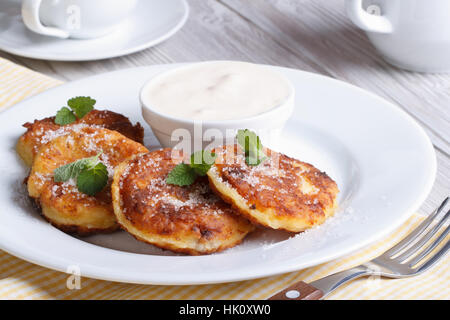 Portion cheese pancakes on a white plate with sour cream closeup horizontal - Stock Photo
