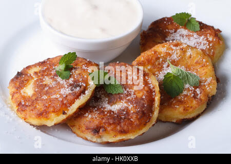 Pancakes with cheese on a white plate with sour cream closeup. a top view of a horizontal - Stock Photo