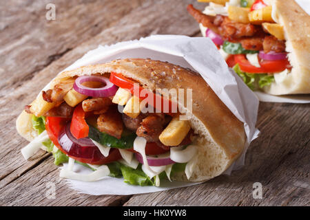 Shawarma in pita bread wrapped in paper close-up on the table horizontal - Stock Photo