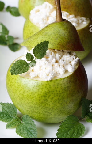 Breakfast: ripe pears with cottage cheese and mint on a white plate closeup vertical - Stock Photo
